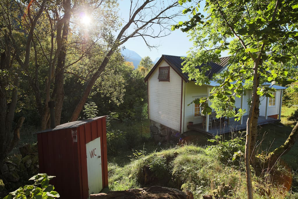 Traditional outhouse and practical porch with afternoon sun.