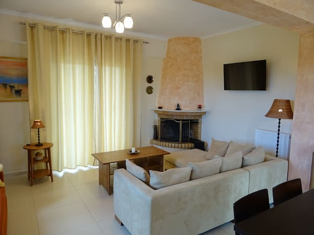The living room with fireplace and flat screen TV, with balcony door to the large veranda overlooking the pool and the surrounding area  - Το σαλόνι με το τζάκι και με τηλεόραση επίπεδης οθόνης, με μπαλκονόπορτα προς τη βεράντα με θέα στην πισίνα