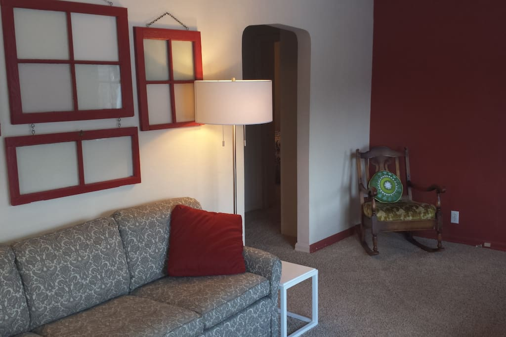 The cozy living room features a couch, 2 chairs and a gas fireplace.