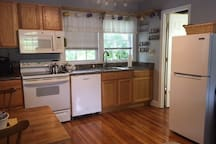 Kitchen features full-sized stove, oven, dishwasher and frig.