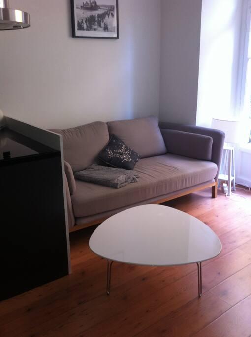 Salon agréablement meublé avec un grand canapé confortable et de poufs pour regarder la TV, une table basse pour l'apéro' !