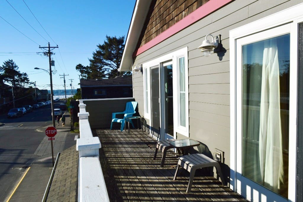 Large upper south facing deck off the living room and master bedroom with ocean views and patio chairs.