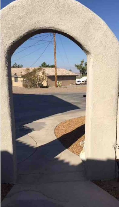 Enter thru archway and courtyard to paved side of house.