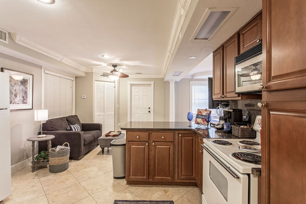 Fully equipped kitchen with imported granite breakfast bar with stools .