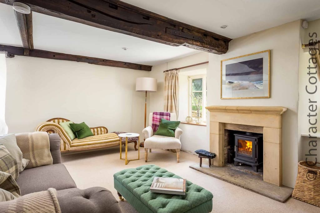 The spacious and stylish living room, with a cosy log burner