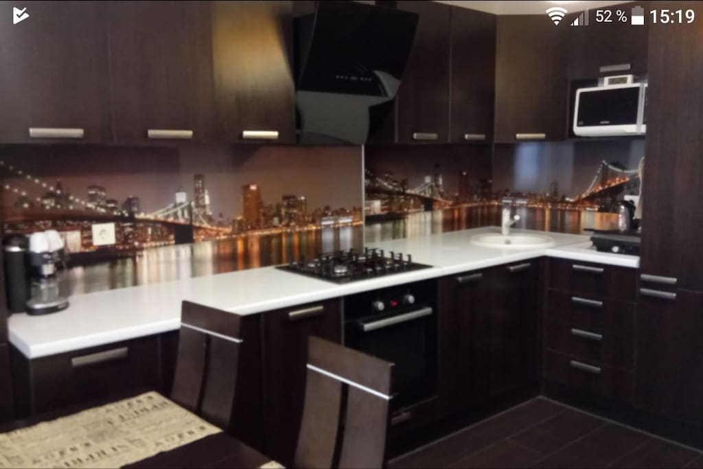 Кухня со всем необходимым: холодильник, плита, духовка, микроволновка, кофеварка, посуда.