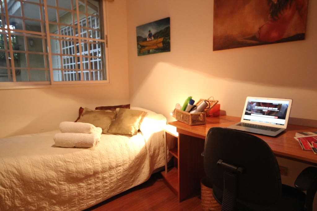 A view of the room. It has a comfortable bed with feather blankets, a big closet and a  great working desktop!