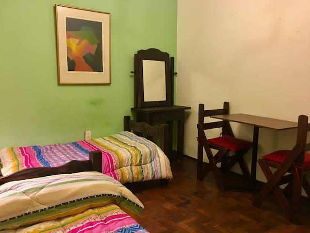 Olegario - Habitación Verde: mesa, sillas, perchero y dresuar.