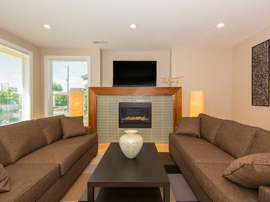 High end furnishings, a gas fireplace, and a large flat screen TV