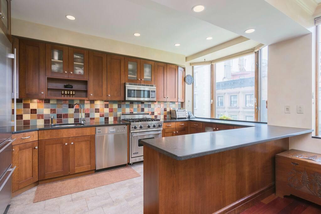 he kitchen has custom teak cabinets, granite countertops, tiled backsplash, Viking stove, Subzero refrigerator & Miele dishwasher.