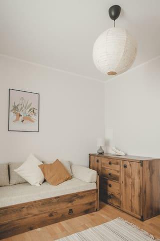 Mniejszy pokój z rozkładaną sofą i komodą