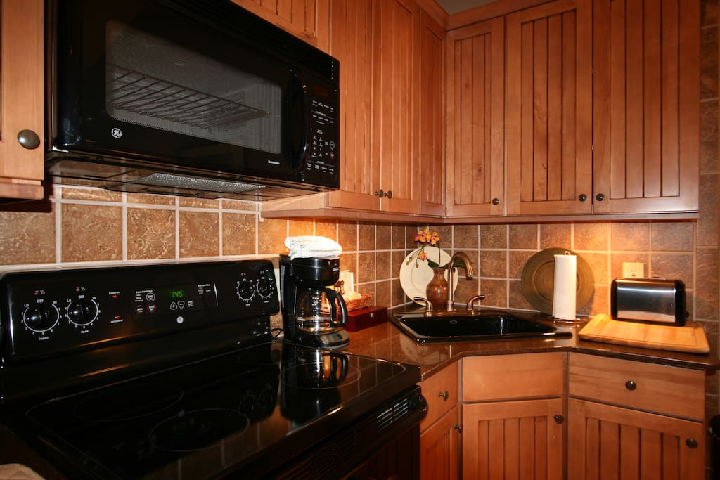 Fully equipped hardwood and granite kitchen area with full stove/oven, full refrigerator/freezer, overhead microwave etc
