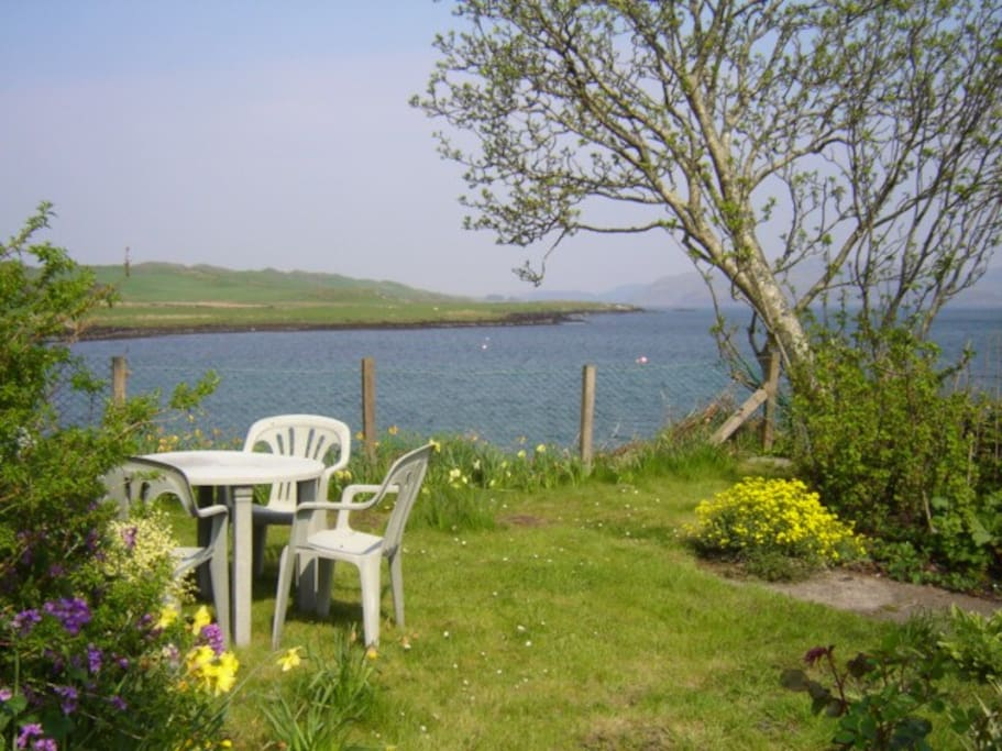 The back garden has a table and chairs at the water's edge, with fantastic views across the bay.