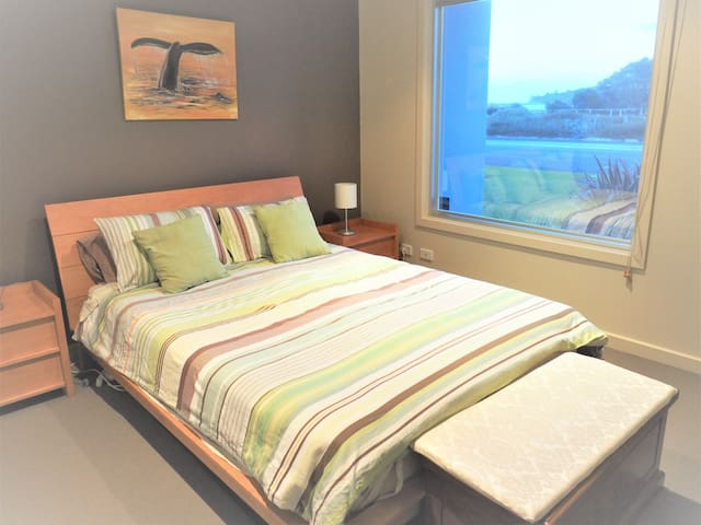 The downstairs bedroom is cosy and private. It boasts views of the beach. There is plenty of wardrobe space and the downstairs bathroom is  adjacent.