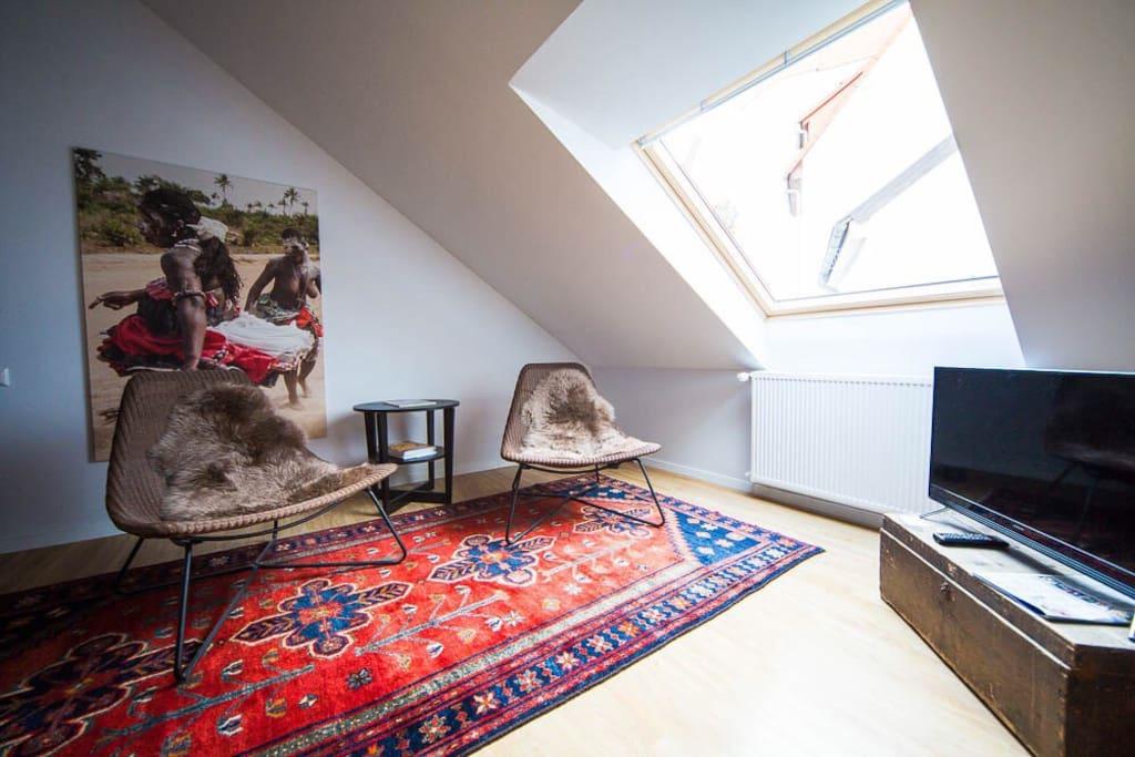 Wohn-/Essbereich mit zwei gemütlichen Sitzgelegenheiten und einem Fernseher