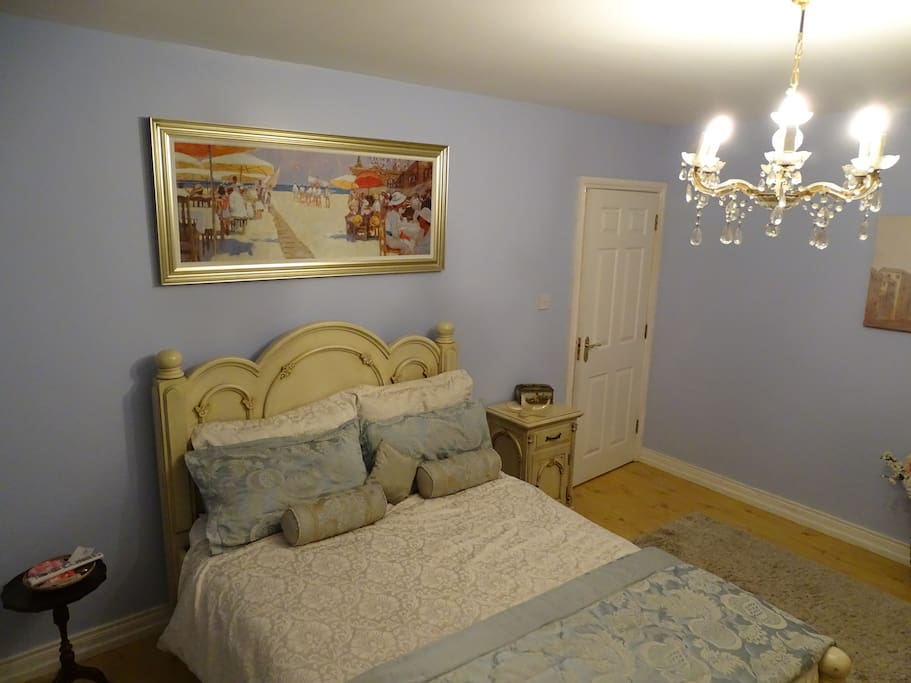 Spacious French themed bedroom with  double bed and chandelier