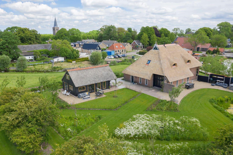 Het vakantiehuisje achter de woonboerderij met op de achtergrond het pittoreske Boksum met de Sint Margrietkerk.