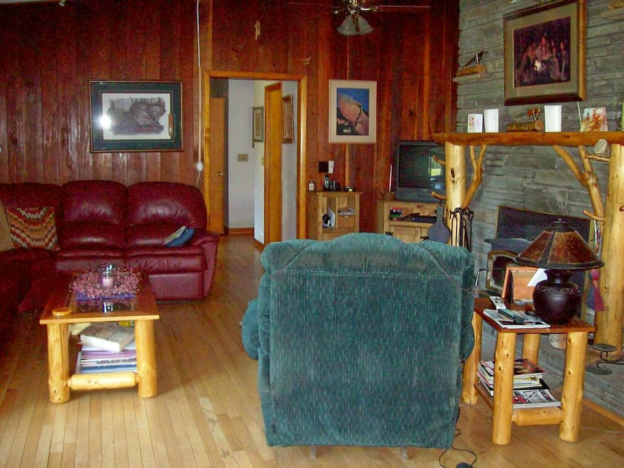 Gathering room with entertainment center, fireplace, books and games.