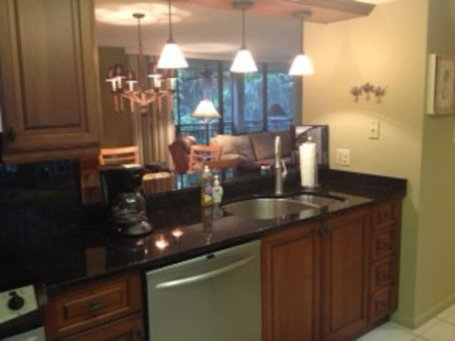 Kitchen has granite counters with full size, stainless appliances.
