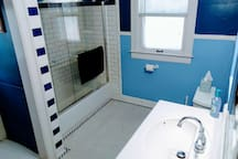 Large recently remodeled bathroom with glass shower doors and subway tile over a new tub.