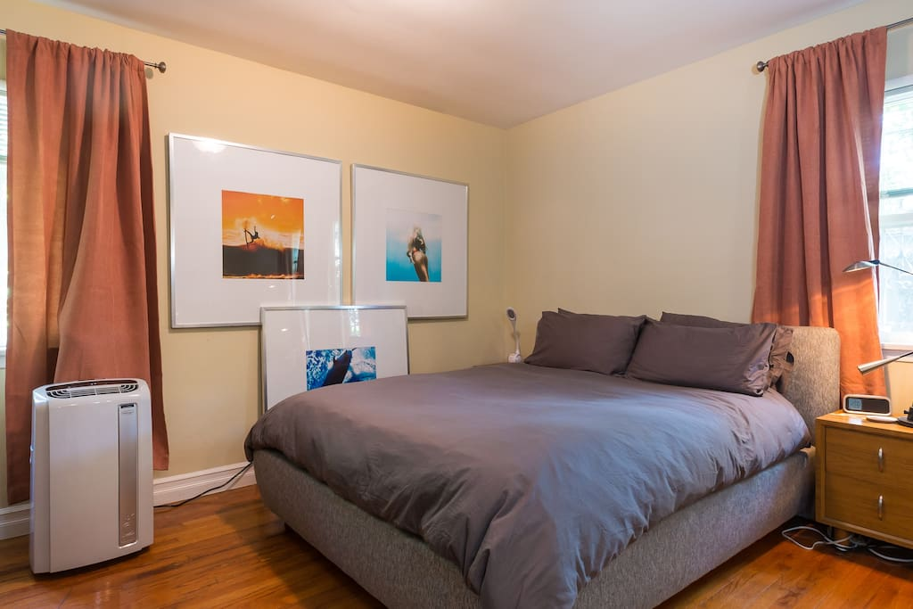Bedroom with queen size bed and AC window unit.