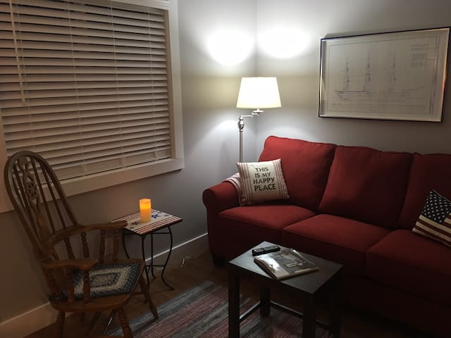 The 4th bedroom/den has a sleeper sofa and Smart TV. There is a door to the back patio and a view of the back woods,