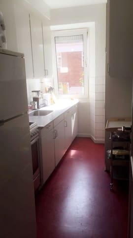 A Copenhagen kitchen. The kitchen has a refrigerator and various White goods. There are gas cooker and oven.