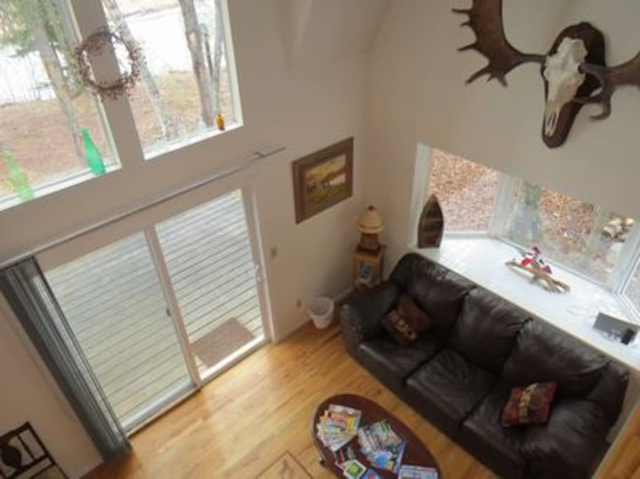Spacious living room with cathedral ceilings, decorated with Alaskan decor, matched with stunning views of the Kasilof River right out your back door.