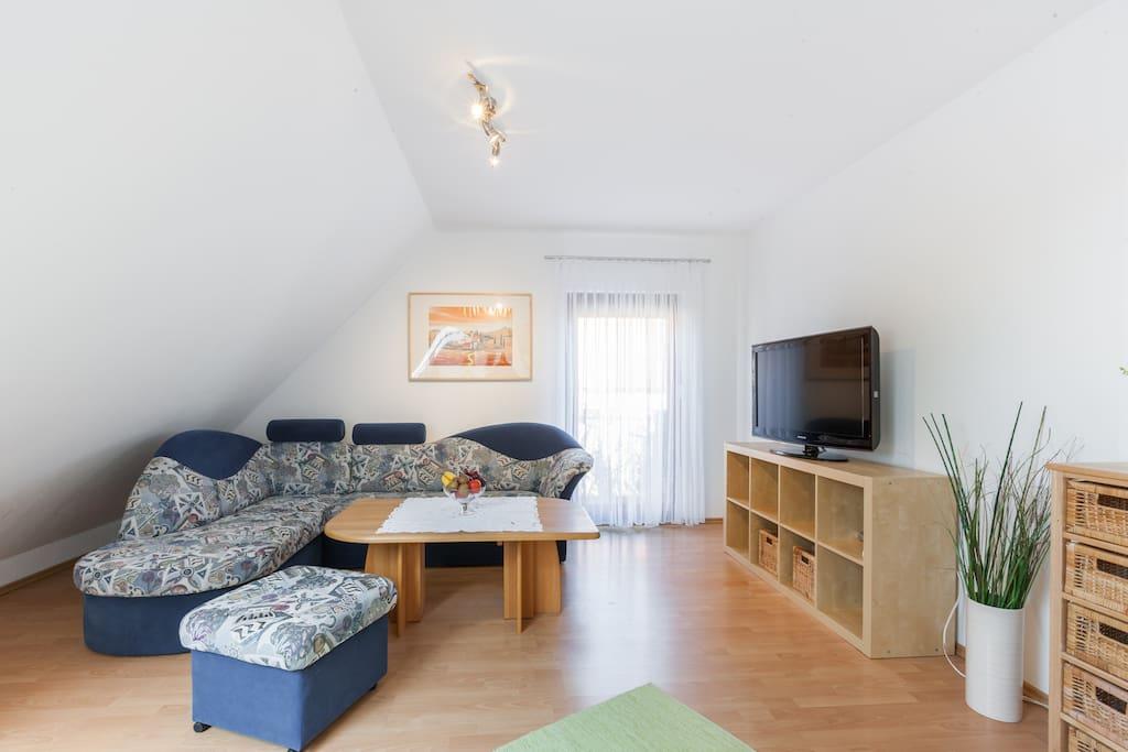 Couch, Fernseher und Tür zum Balkon
