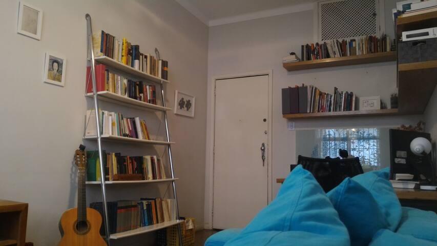 Temos estantes cheias de livros para você desfrutar de um momento sossegado nesse sofá aconchegante.  We have shelves filled with books for you to enjoy a quiet moment in our super cozy couch.