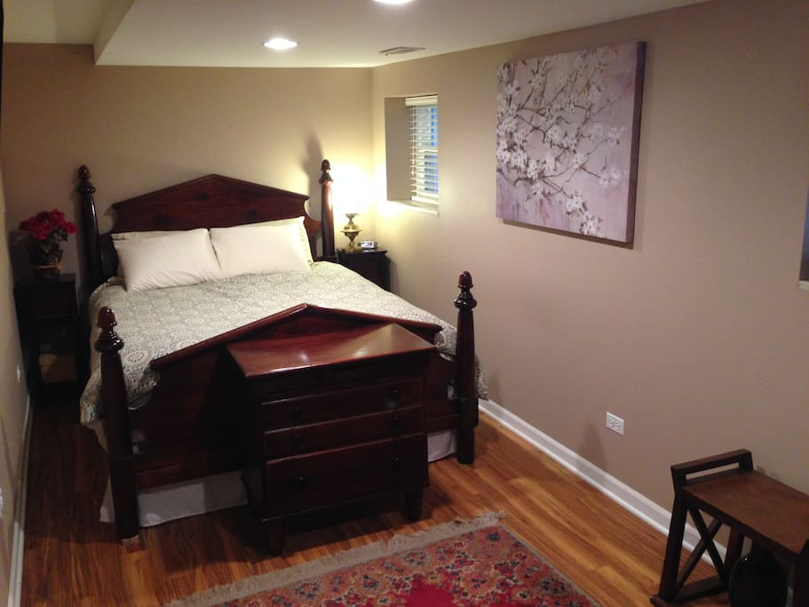 Queen bed with flat screen TV on wall.