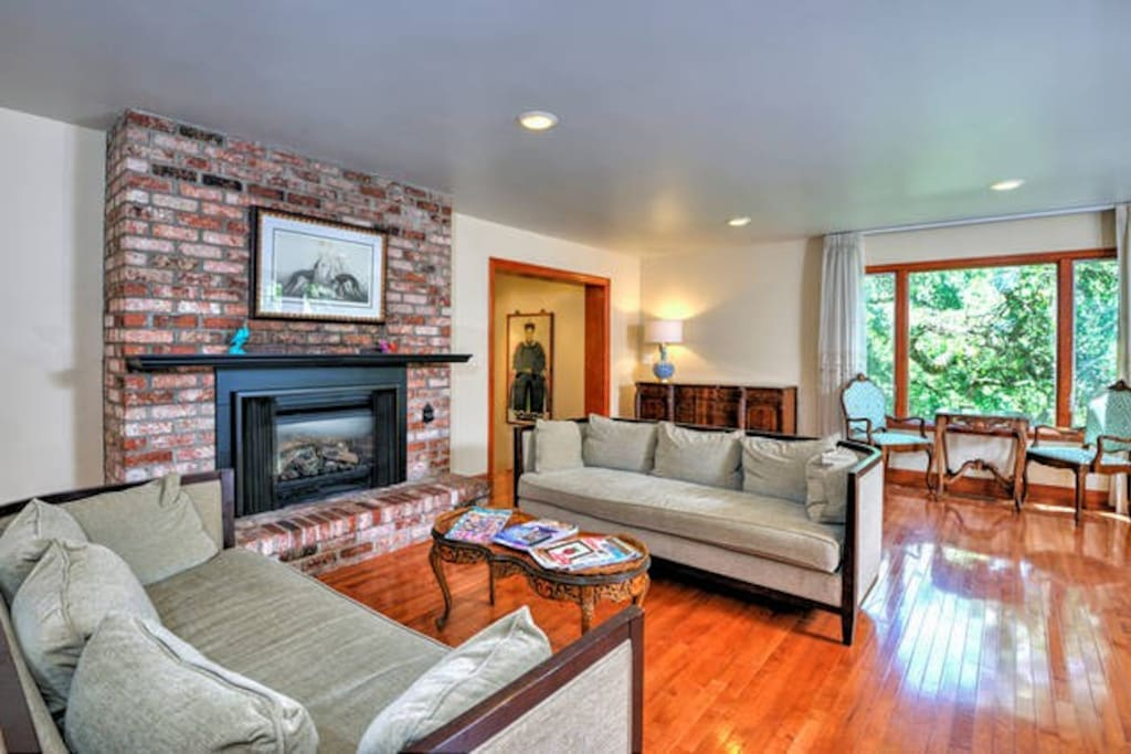 The elegant living room features classy couches, a large fireplace and hardwood floors.