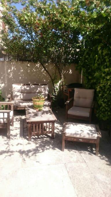 Salon de jardin sous pergola avec plancha et barbecue