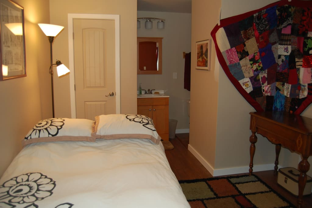 Bed, reading light, closet, with the bathroom behind to the right