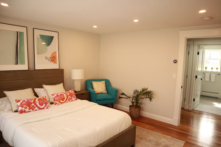 The Queen bed and the chair in Bedroom One.  The soft lighting helps you relax after a long day.