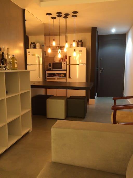 Sala de estar, hall de acesso e cozinha. Parte do sofá, bar, mesa de jantar suspensa, cadeiras e pufes, geladeira com freezer, forno de microondas.