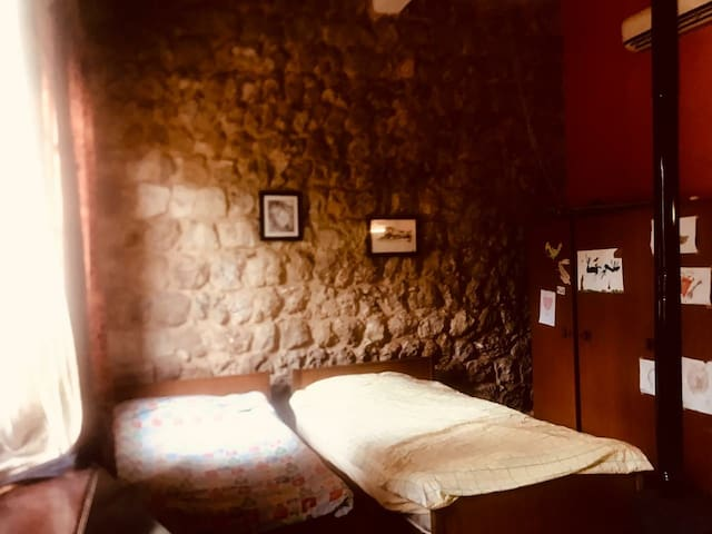 This is the main bedroom 16 m2 with a private bathroom and a laundry room next to it. Air conditioning system is available. There is a desk. It has two stone walls.