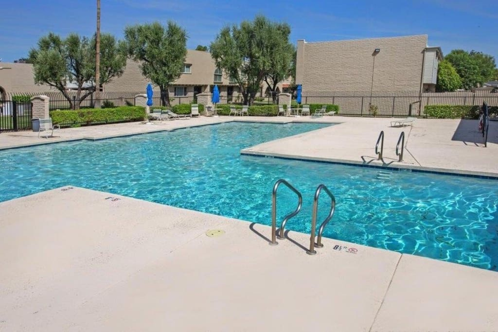 Pool with umbrellas and lounge chairs. Access is secured with a fob located in the townhouse.