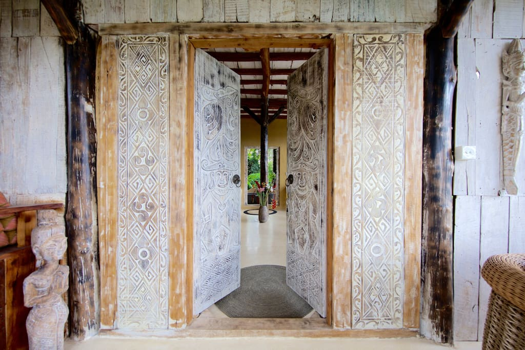 Enter through the solid teak carved doors