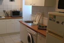 cuisine avec plaque de cuisson, four, four micro onde, réfrigérateur avec compartiment congélateur et lave linge