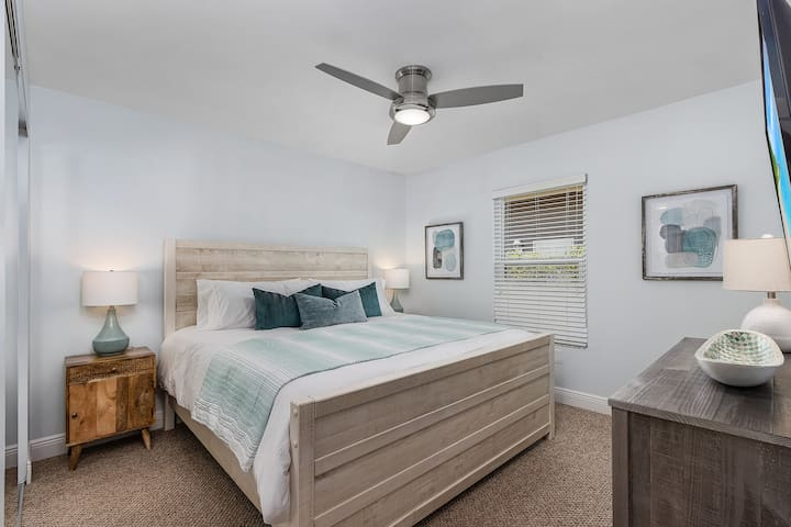 Guest bedroom with king size bed, large closet and smart TV.