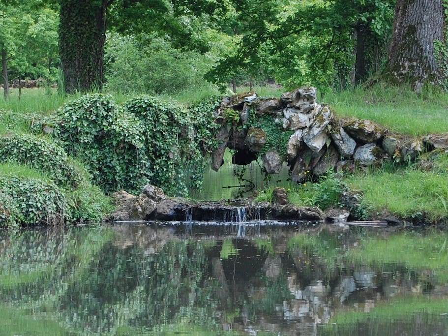 Waterfall over the pond in the meadow. Cascade au dessus du lac dans le parc.