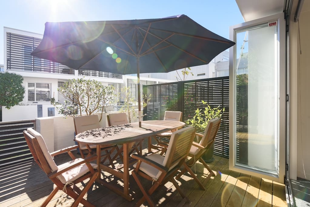 Sunny courtyard with 6 seater outdoor furniture and sun umbrella