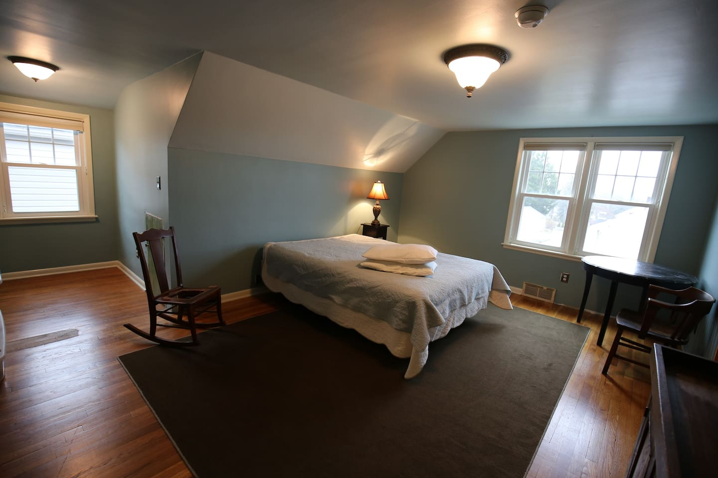 Simple well lit space with queen sized bed,  hangers and hook rack behind the door, a table,  a desk,  a rocker,  and two chairs.