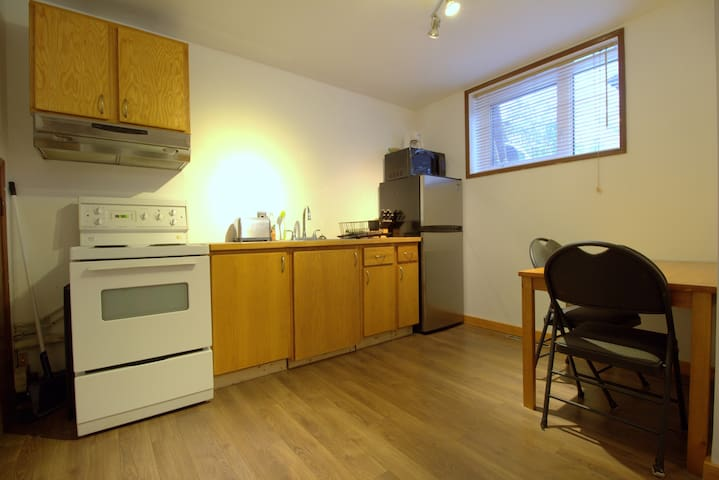 Kitchen with large window and lots of light. Apartment size 4 burner stove, refrigerator, table, pots, pans, dishes, coffee maker, tea pot, etc.