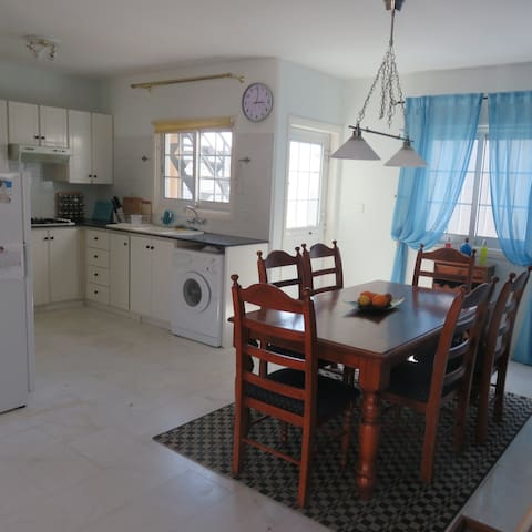 Dining room and kitchen, with large fridge, washing machine and cooker