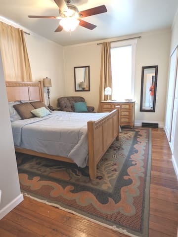 Master bedroom, original pine wood floors, ceiling fan, queen size memory foam mattress, clean linens after every stay, dresser, walk in closet, hangers, ironing board, and iron.