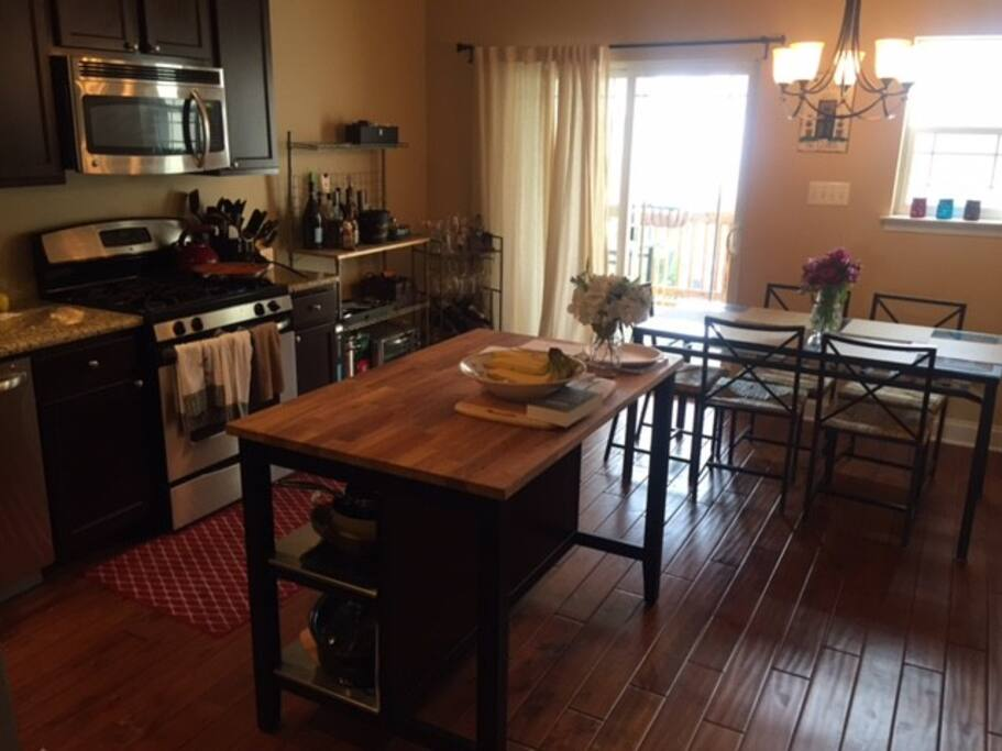 spacious kitchen with island and table that seats 6