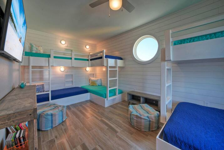 Super fun and super cute bunk room.  Look at that port hole window!!   5 Twins and 1 Queen.  TV.  Closet.
