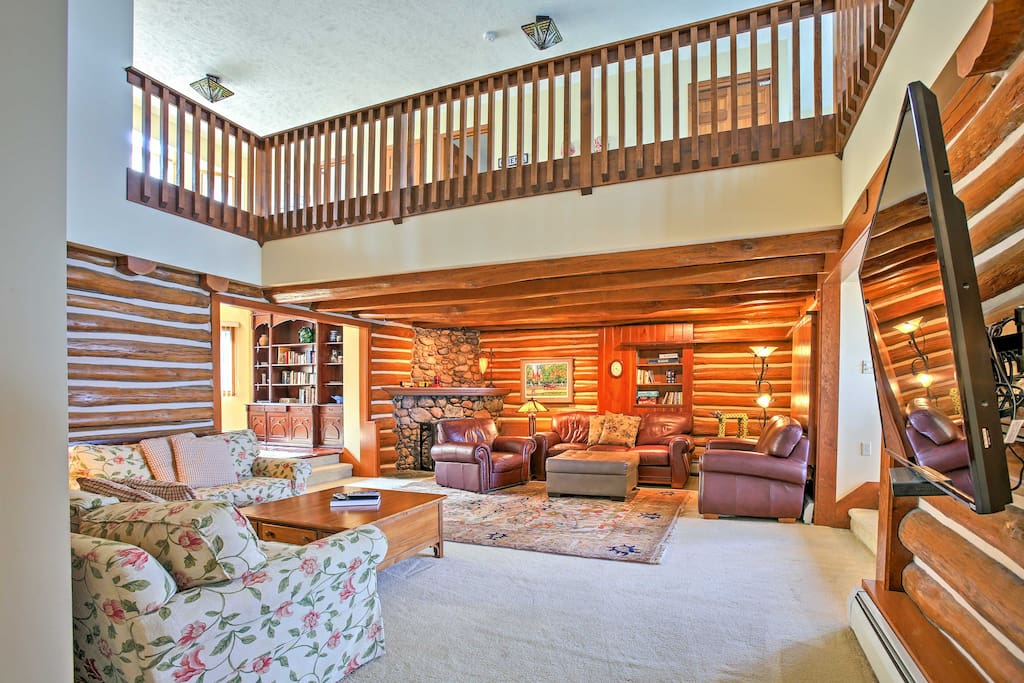 The living room features the original wood walls of the log home, 3 plush couches, 2 armchairs, and a 60-inch flat-screen cable TV.
